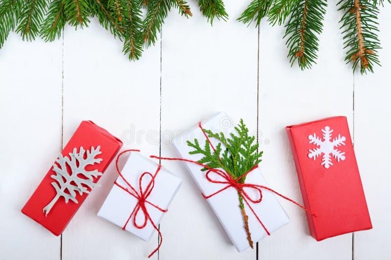 ` S, jultema för nytt år Grön gran förgrena sig, gåvaaskar på vit träbakgrund royaltyfri foto