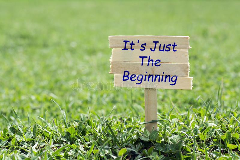It`s just the beginning. Wooden sign in grass,blur background stock photography