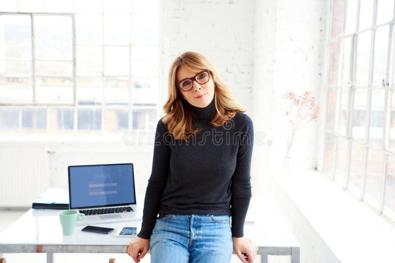 S?ker attraktiv aff?rskvinna som kopplar av p? kontorsskrivbordet, medan se kameran och att le arkivfoto