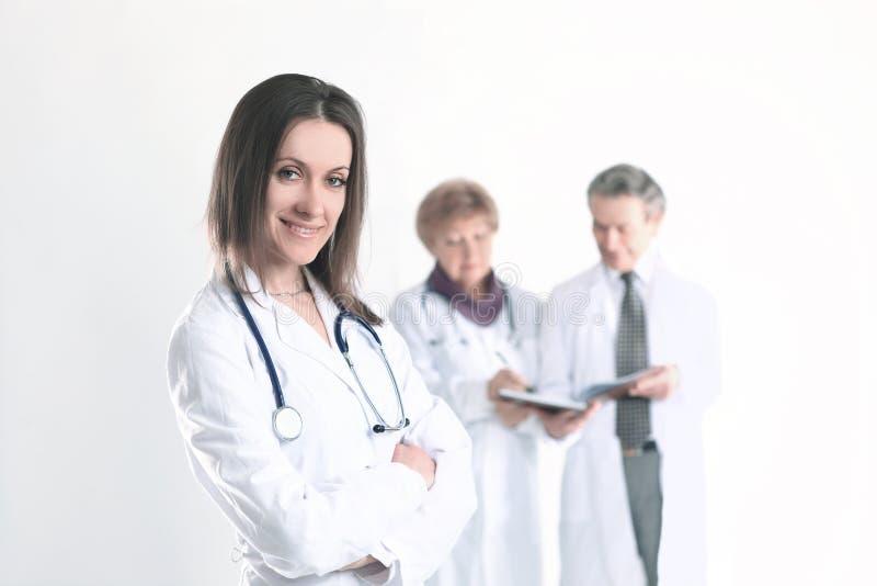 S?ker kvinnlig doktorsterapeut p? suddig bakgrund av kollegor arkivbild