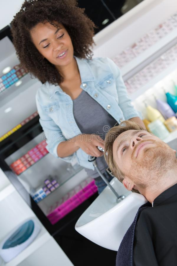 ` S Kunde des Friseurs waschendes Haar stockfotos