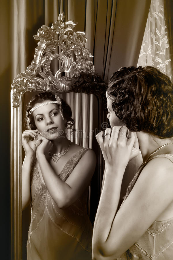 1920s lady in mirror. Stunning vintage 1920s woman looking in an antique mirror royalty free stock photos