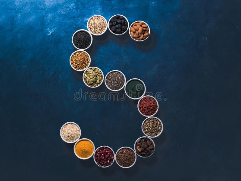 S letter of superfoods in bowl on blue background stock image