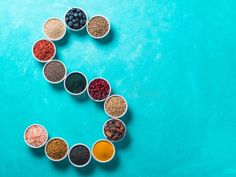 S letter of superfoods in bowl on blue background royalty free stock photos