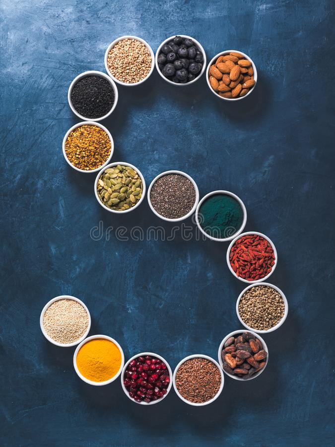 S letter of superfoods in bowl on blue background stock images