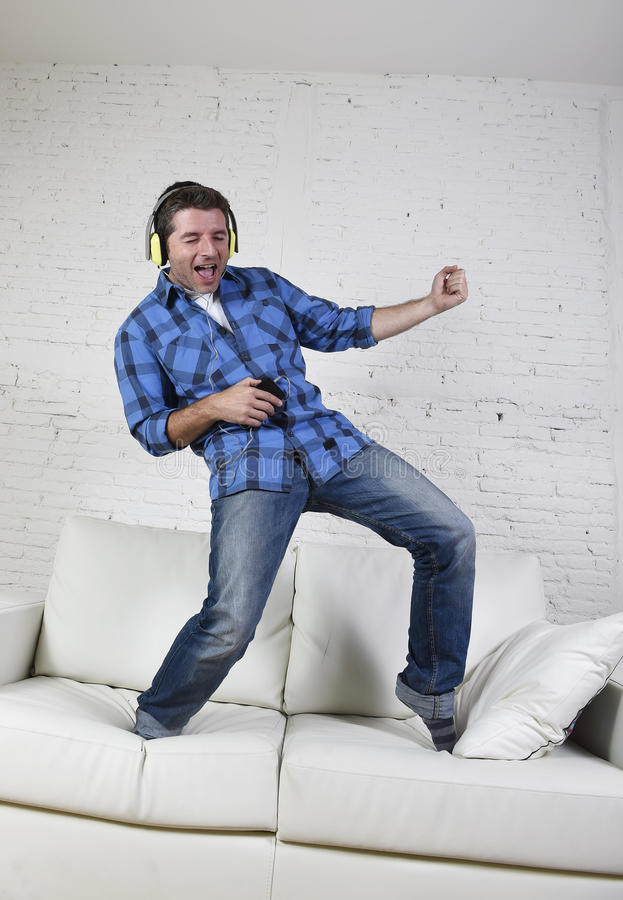 20s lub 30s mężczyzna słucha muzyka na telefonie komórkowym z hełmofonami bawić się lotniczą gitarę skakał na leżance obraz royalty free
