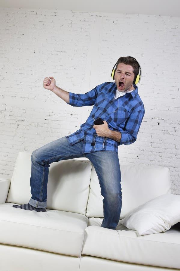 20s lub 30s mężczyzna słucha muzyka na telefonie komórkowym z hełmofonami bawić się lotniczą gitarę skakał na leżance zdjęcie royalty free
