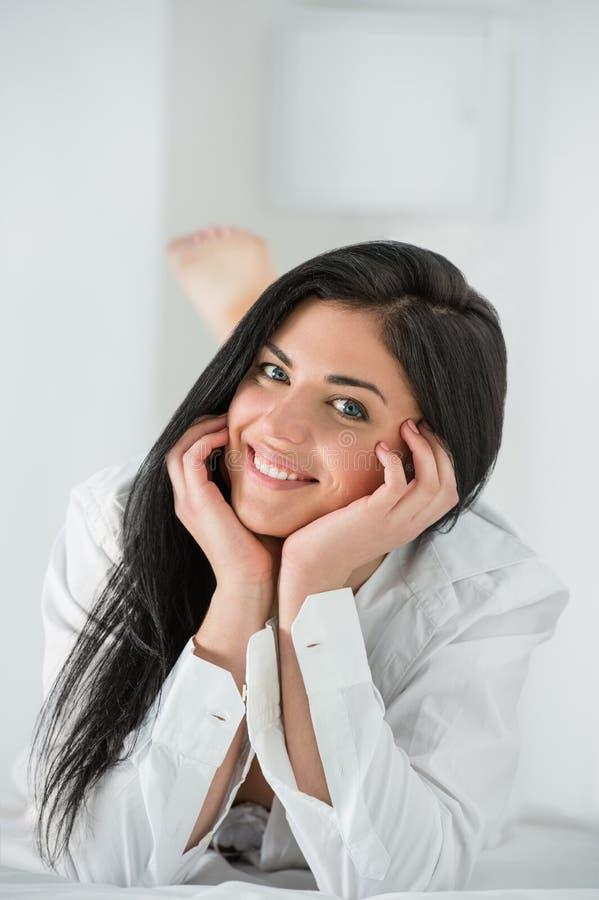` S Mann der jungen hübschen Frau tragendes Hemd auf Bett lizenzfreie stockbilder