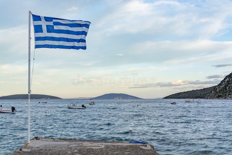 S?mbolo nacional de Gr?cia, da bandeira grega azul-branca, da ?gua do mar e do c?u azul, espa?o da c?pia imagem de stock royalty free