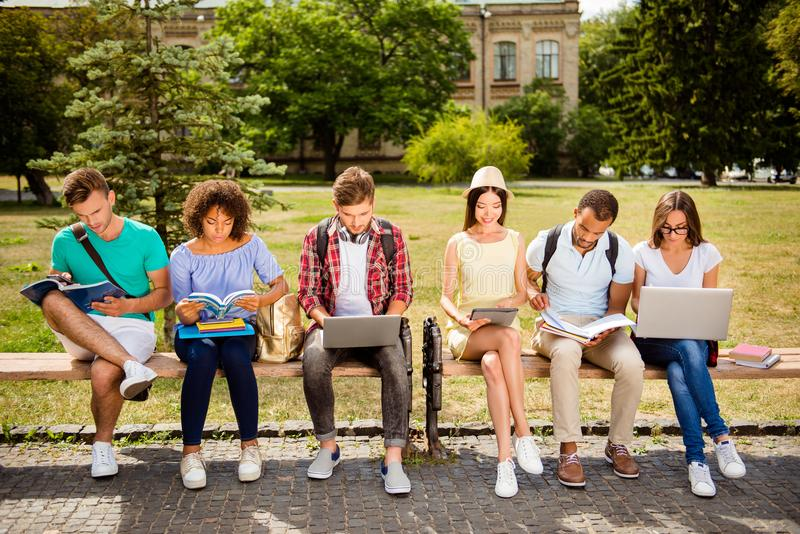 It`s more easy together! Six cheerful classmates are sitting on royalty free stock photos