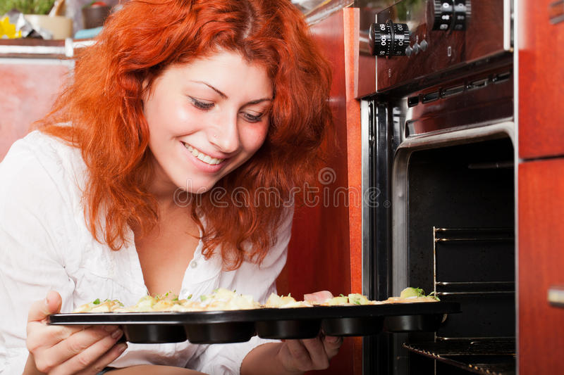 It's muffins time!. Young lady is about to put blueberry muffins into oven stock photos
