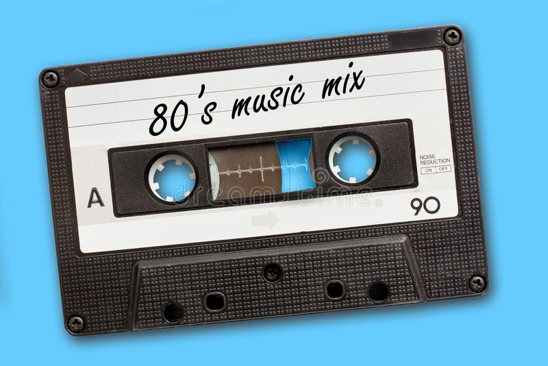80`s music mix written on vintage audio cassette tape, blue background stock photography