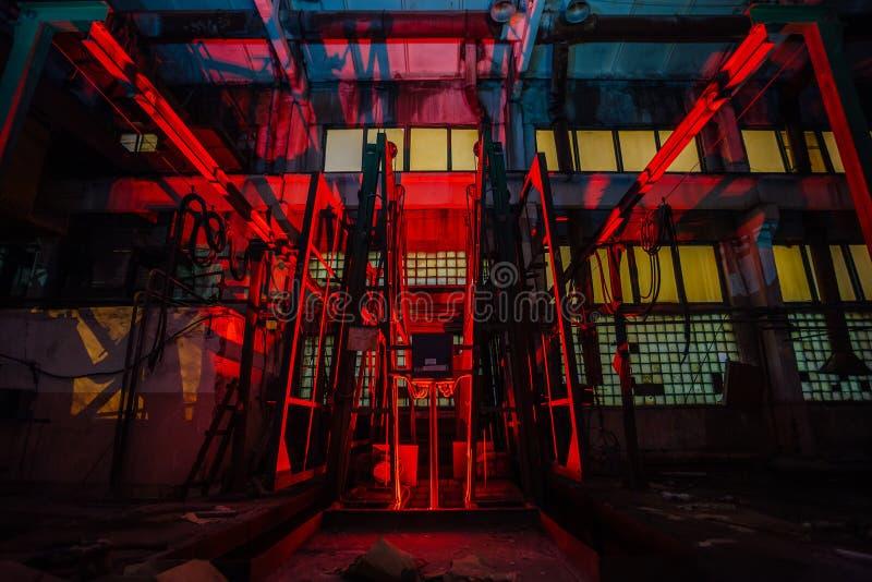 's Nachts verlaten baksteenfabriek Oude roestbaksteen vormende machine en transporteur verlicht door kleurenlicht Abstract indust royalty-vrije stock foto's