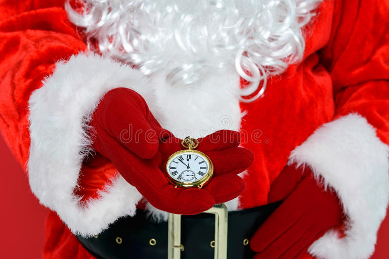 It's nearly Christmas time. Santa Claus or Father Christmas checking his gold pocket watch to see if it's time for Christmas stock photo