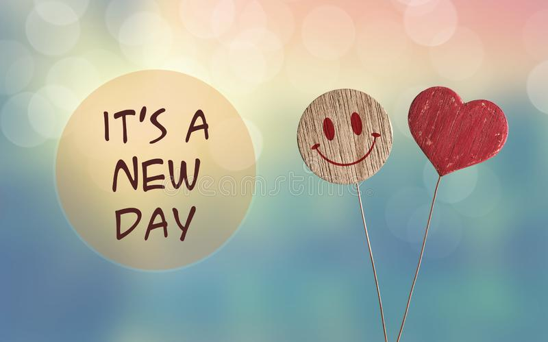 It`s a new day with heart and smile emoji. It`s a new day with wooden heart and smile emoji on bokeh light background royalty free stock photo