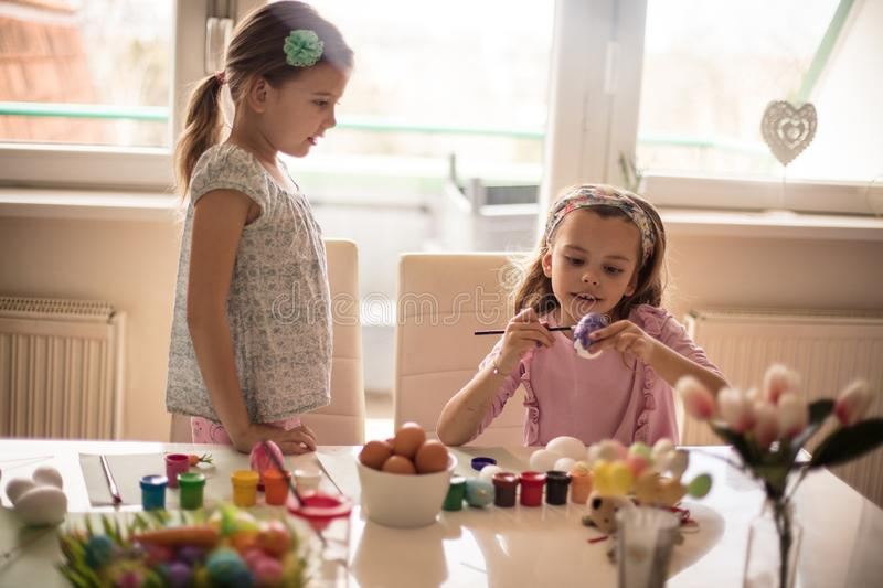 It`s nice to do this, this Easter will be wonderful full of colors. Little girls coloring Easter egg royalty free stock image