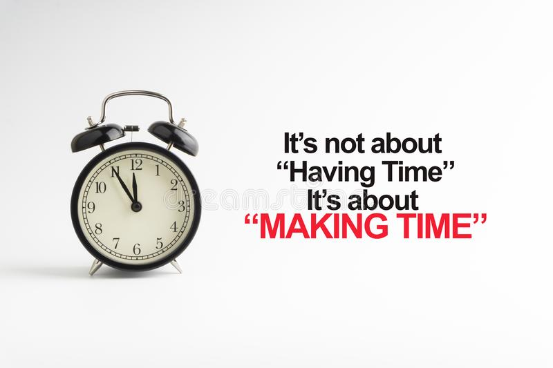 IT`S NOT ABOUT HAVING TIME IT`S ABOUT MAKING TIME inscription written and alarm clock on white background royalty free stock photos