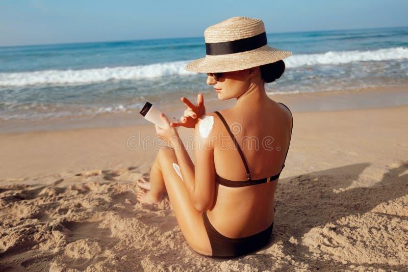 S?o?ce ochrona, dziewczyna u?ywa sunscreen skrytka jej sk?ra zdrowa Seksowna młoda kobieta w bikini mienia butelkach sunscreen w  obraz royalty free