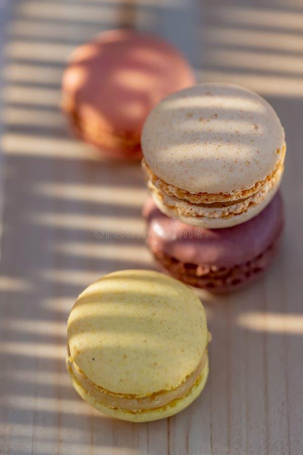 S?odki francuz barwi? macaroons na nieociosanym drewnianym stole Wy?mienicie cukierki dla herbaty zdjęcia royalty free