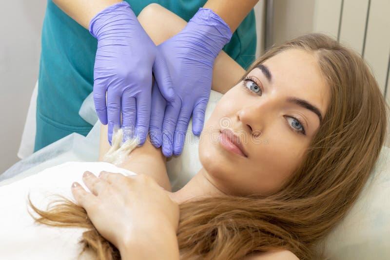 S?odzenie: epilacja z liquate cukierem przy pach? Kobieta dostaje cukrową epilację w salonie zdjęcia royalty free