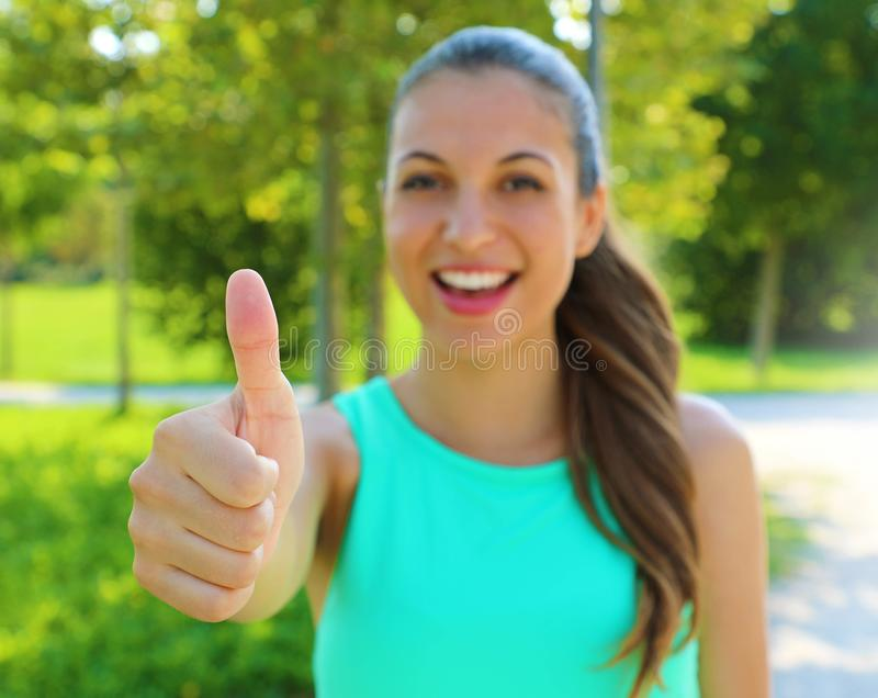 It`s ok! I like it! Portrait of winner girl showing thumb up. Positive smiling fitness healthy woman outdoor. Focus on the hand royalty free stock image