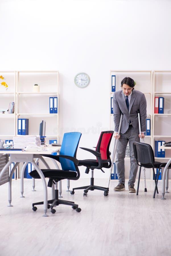 S?rad manlig anst?lld f?r ben som arbetar i kontoret arkivfoton