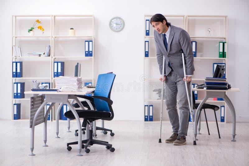 S?rad manlig anst?lld f?r ben som arbetar i kontoret arkivfoto