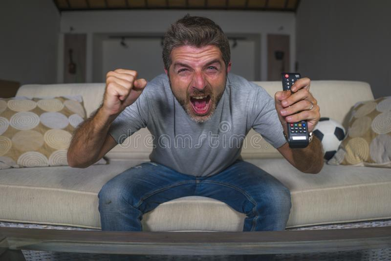 30s or 40s football fan man watching soccer game celebrating his team scoring goal crazy happy screaming cheering his team sitting royalty free stock image