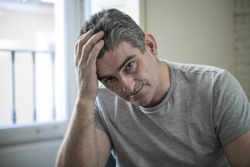 Sad and worried man with grey hair sitting at home couch looking. 40s or 50s sad and worried man with grey hair sitting at home couch looking depressed and royalty free stock photography
