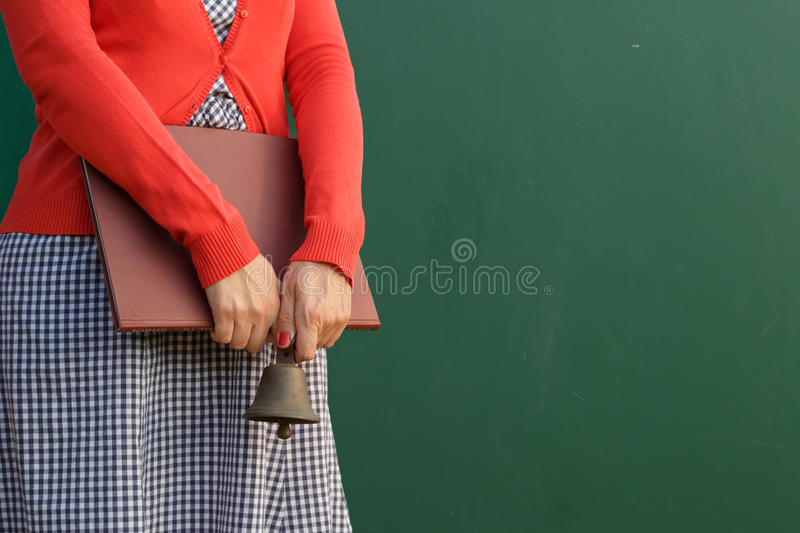It's school time. Back to school. Teacher holding books and bell in fron of the chalkboard stock photography