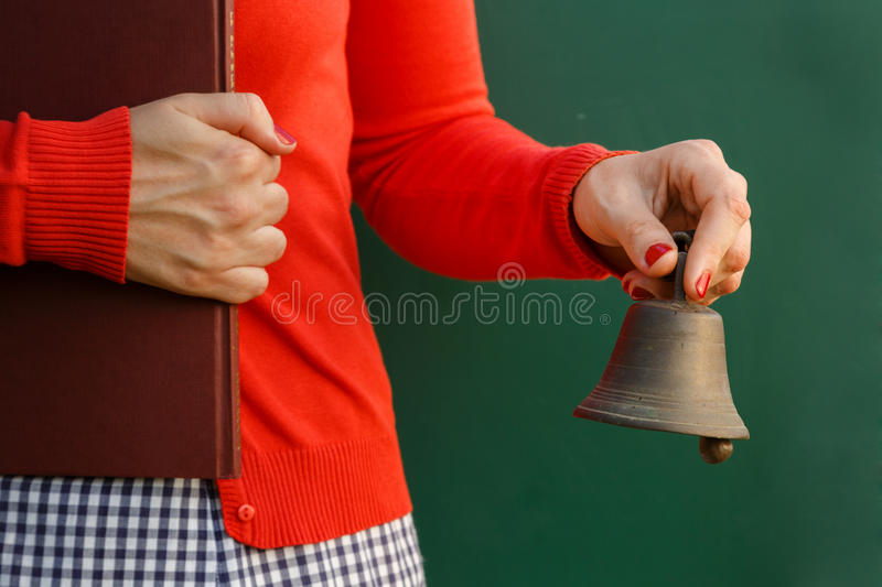 It's school time. Back to school. Teacher holding books and bell in fron of the chalkboard royalty free stock images