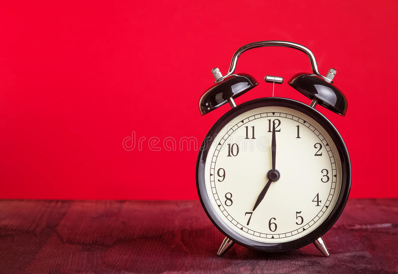 It`s seven o`clock already, time to wake up for love, vintage old black metallic alarm clock on red background stock images