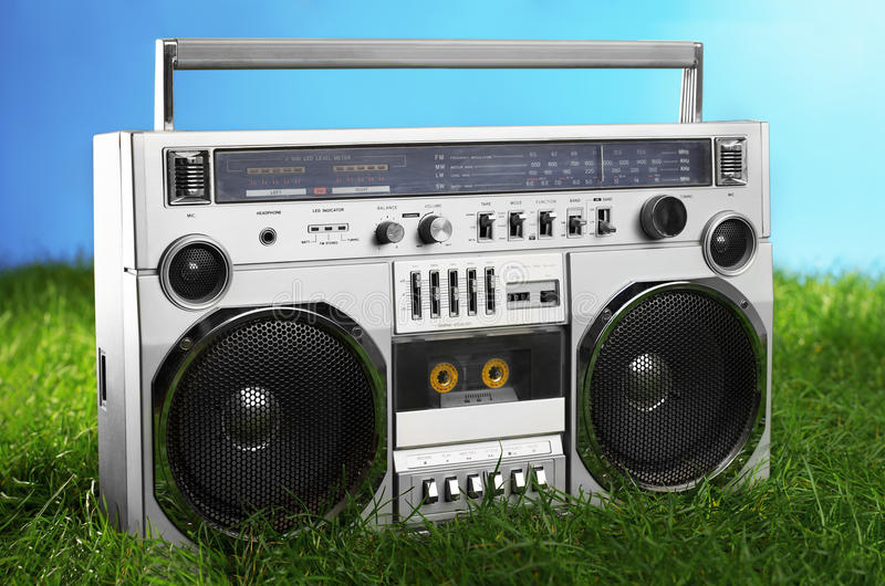1980s Silver boom box blaster over fresh green grass. Retro styled boom box blaster on fresh green grass, blue background royalty free stock photography