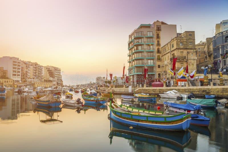 ` S StJulian, Мальта - традиционные красочные рыбацкие лодки Luzzu на Spinola преследуют стоковое фото rf
