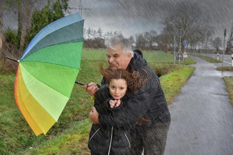 Father and daughter in stormy weather. It`s stormy and rainy weather. Father tries to open an umbrella to protect himself and his daughter stock photo