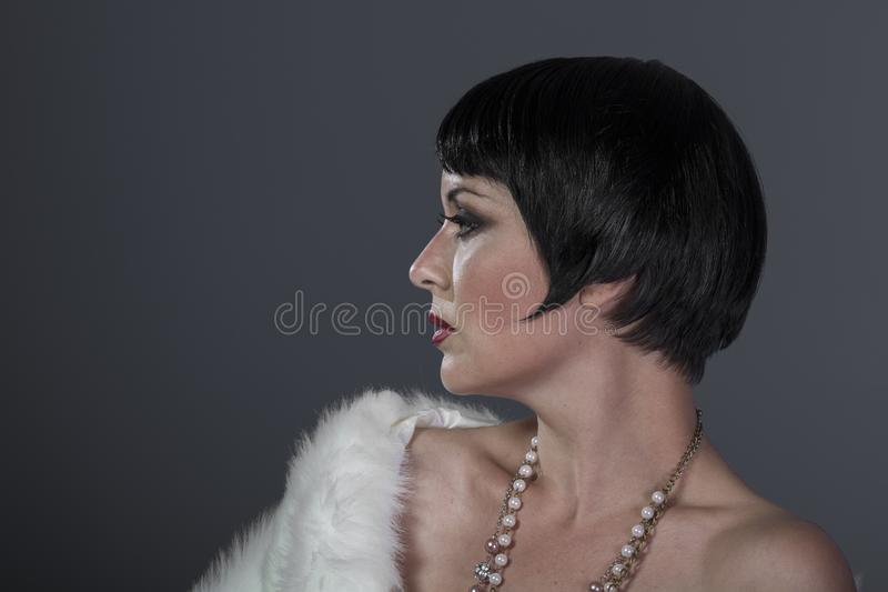 1920s style brunette dancer with short hair and jewelry. She is stock image