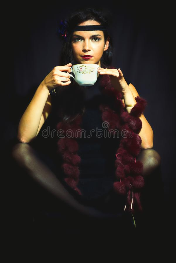 1920s style woman drinks from the cup.  royalty free stock images