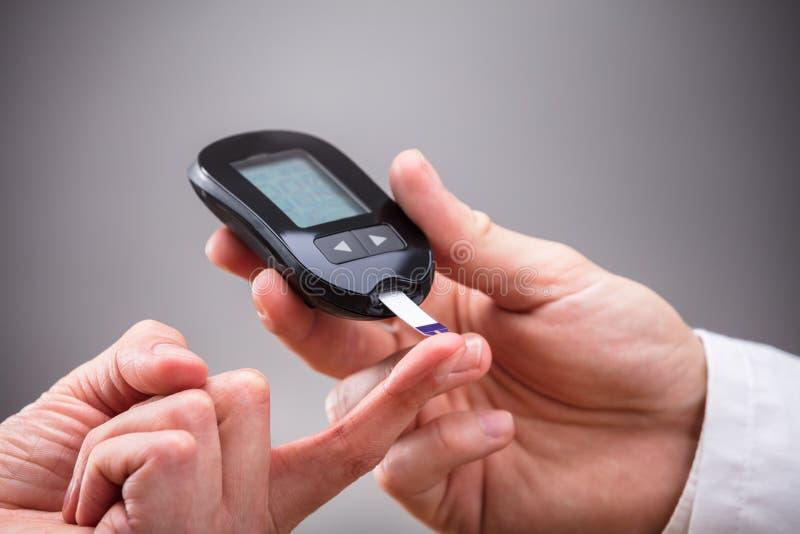 ` S Sugar Level With Glucometer för doktor Checking Patient royaltyfri bild