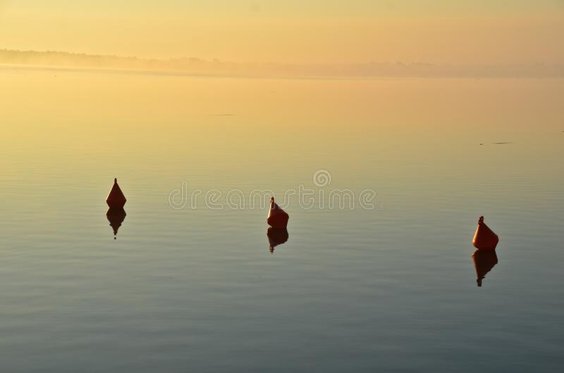 Three buoys in calm water in golden evening light. It`s a sunset at a lake in Poland a silhouette of three buoys  in front of golden light, a perfect background stock photos