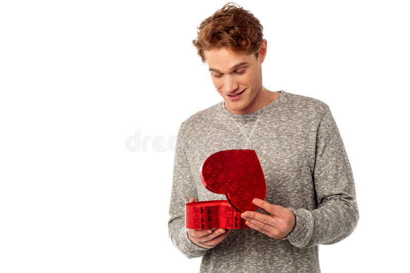 It's really surprised gift. Casual young man opening his valentine gift stock images