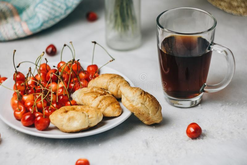 S?t k?rsb?r f?r sund ljus frukost med giffel p? en platta bukett i en vas med spikelets av vete isolerad teawhite f?r bakgrund ko arkivfoto
