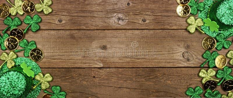 S:t Patricks Day, dubbelsidig kantlinje av schamprockar, guldmynt och leprechaunhatt, toppvy över en träbakgrund med kopieringsut arkivfoto