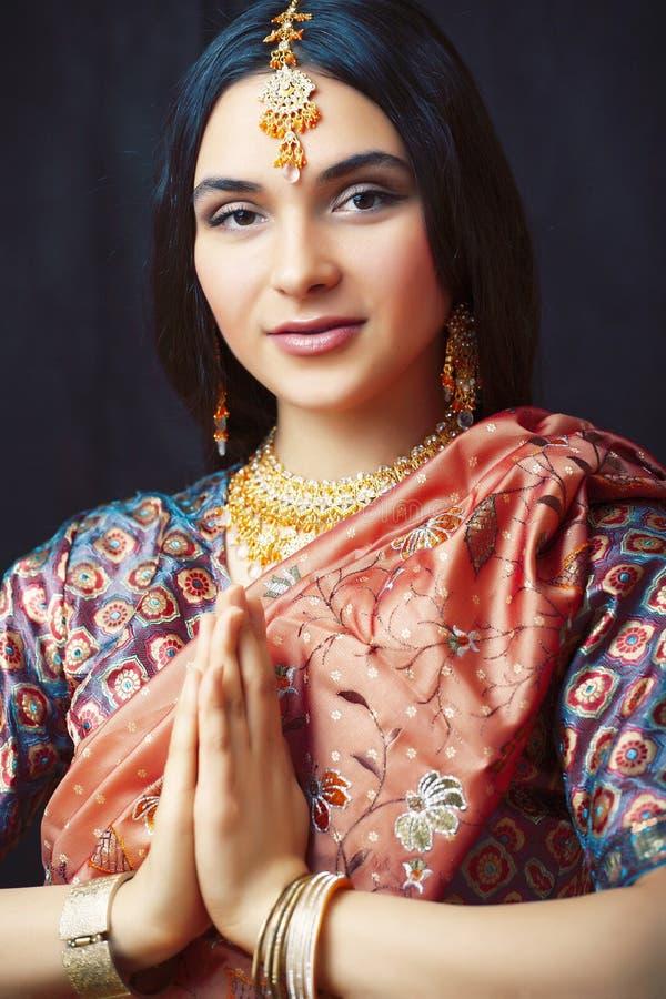 S?t verklig indisk flicka f?r sk?nhet, i att le f?r sari som ?r gladlynt, smycken som skiner, livsstilfolkbegrepp arkivbild
