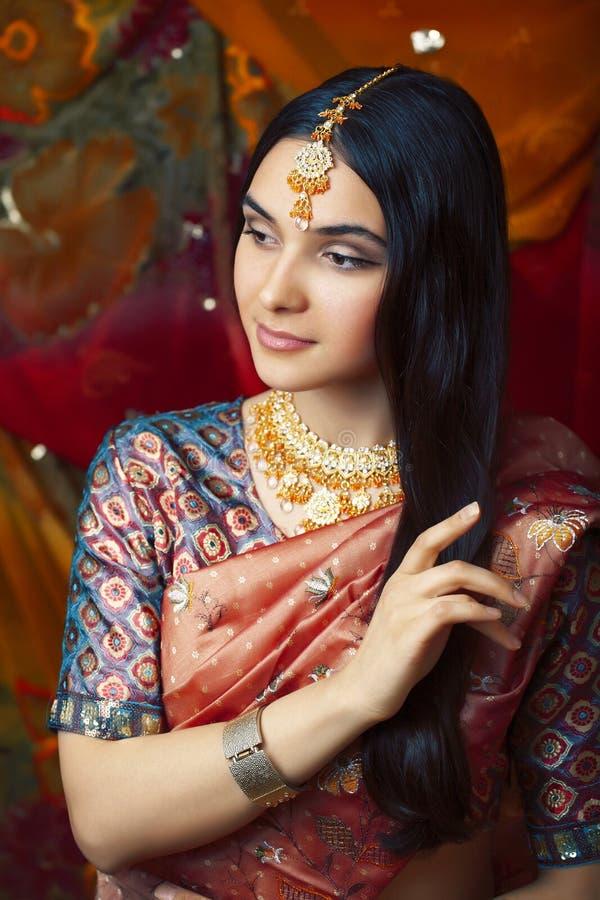 S?t verklig indisk flicka f?r sk?nhet, i att le f?r sari som ?r gladlynt, smycken som skiner, livsstilfolkbegrepp royaltyfri foto