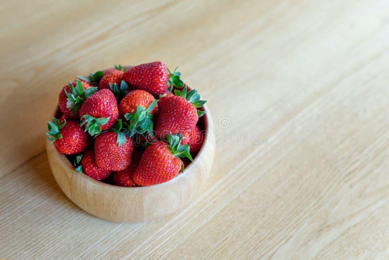 S?ta nya saftiga organiska mogna jordgubbar i tr?bunke p? tr?tabellyttersida hemma arkivfoto