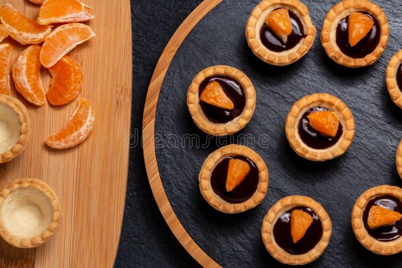 S?ta tartlets med choklad och skivor av tangerin p? en matr?tt av naturligt kritiserar f?r att tj?na som, b?sta sikt royaltyfri bild