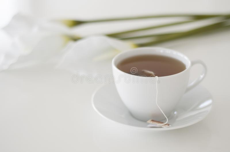 It`s tea time! English Afternoon tea, a white teacup and white arum flowers on a background.  royalty free stock photography