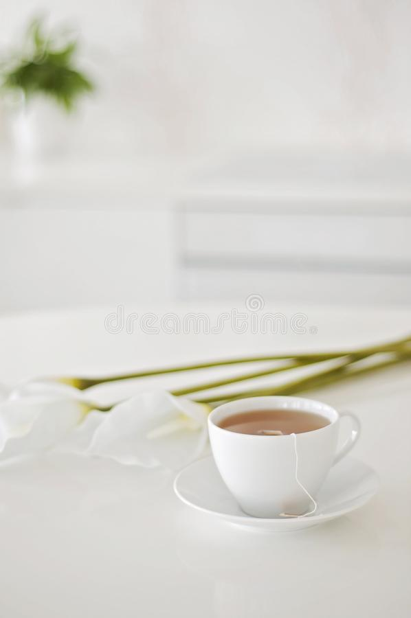 It`s tea time! English Afternoon tea, a white teacup and white arum flowers on a background.  stock photography