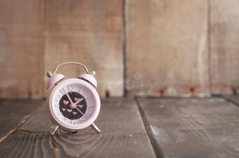 It`s time for love. Pink alarm with heart shapes on wooden background royalty free stock images