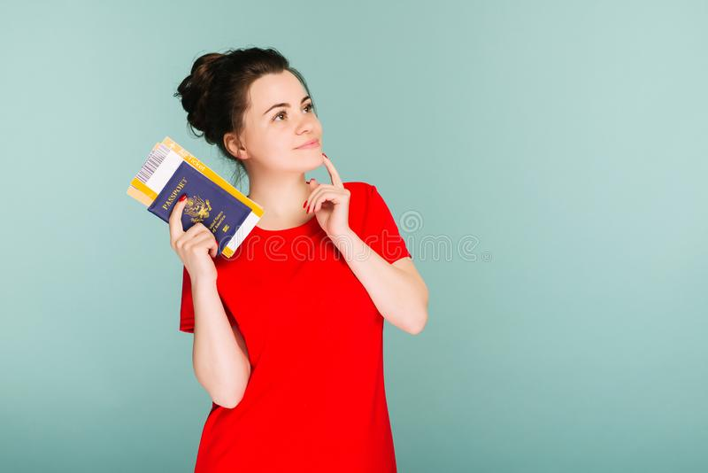 A modern trendy smiling woman in red dress with air tickets and a passport in her hand stock photography